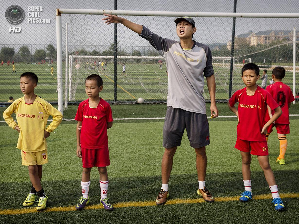 Китай. Цинъюань, Гуандун. 13 июня. Тренер даёт указания. (Kevin Frayer/Getty Images)