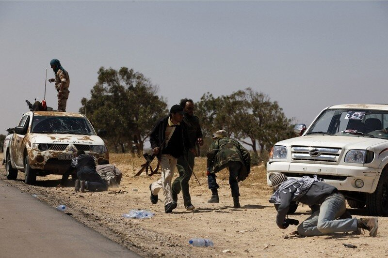Rebels run and take cover from explosions during a fight with troops loyal to Muammar Gaddafi outside Brega in eastern Libya