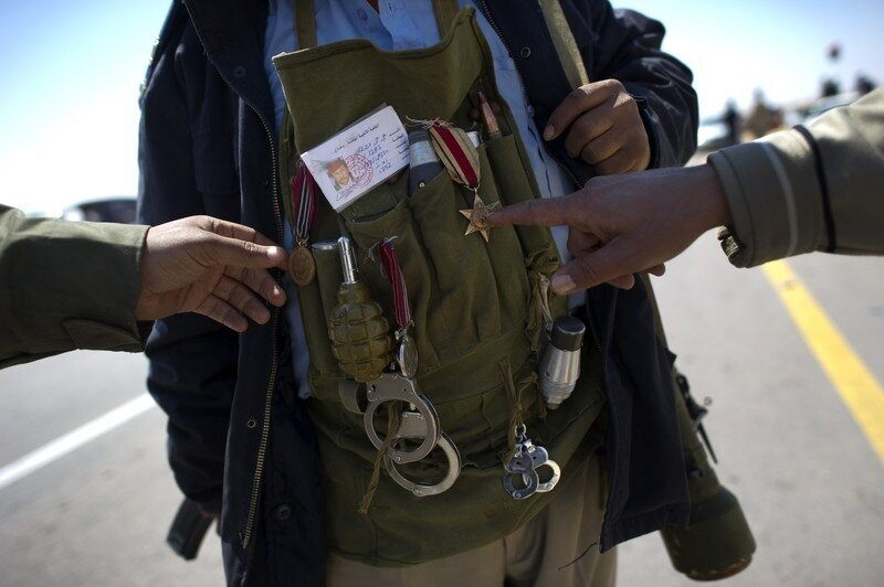 A Libyan rebel points the medal of a com