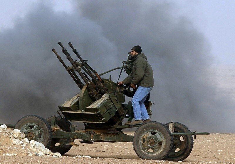 Rebel fighters return fire during shelling by soldiers loyal to Libyan leader Muammar Gaddafi in a battle near Ras Lanuf