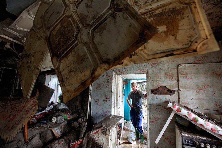 A local resident looks at the debris of a house damaged by floods in Krymsk