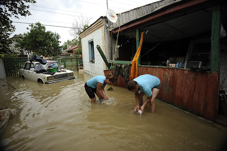 Local people work amidst the debris of a house in Krymsk