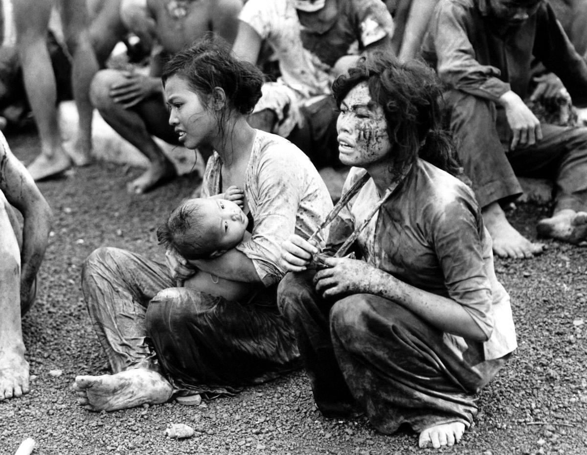Изнеможенные мирные люди, которые выползли из подземных укрытий после двухдневной бомбардировки и тяжелых боев в окрестностях города Dong Xoai