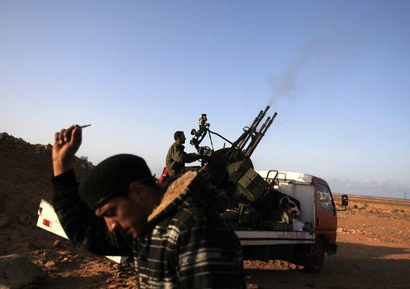 Anti-Gaddafi rebels shoot after hearing an incoming aircraft at a checkpoint near the oil facility of Ras Lanuf