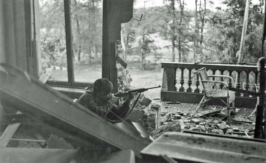 """Squadron Sergeant Major Watt, """"B"""" Squadron, The Glider Pilot Regiment, takes aim with an American M1 carbine from the first floor front balcony of the Hartenstein Hotel."""