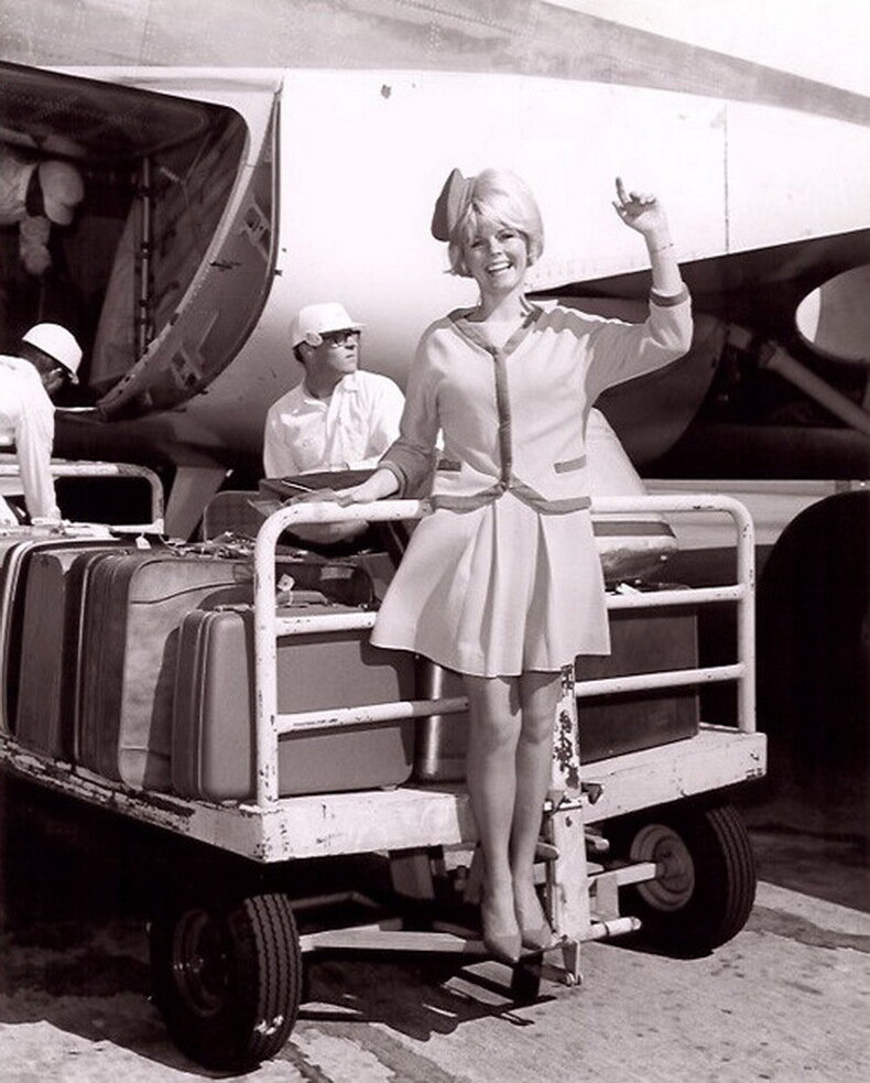 vintage_flight_attendant_riding_baggage_cart.jpg