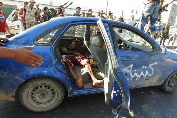 Libyan rebel fighters stand beside a car transporting an injured comrade during a fight for the final push to flush out Muammar Gaddafi's forces in Abu Salim district in Tripol