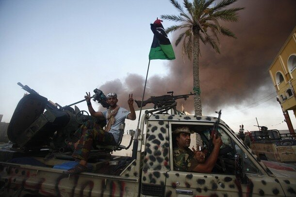 Libyan rebel fighters flash the victory sign during a fight for the final push to flush out Muammar Gaddafi's forces in Abu Salim district in Tripoli
