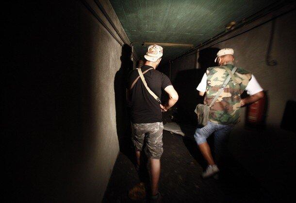 Rebel fighters walk through a tunnel in the ransacked Bab al-Aziziya compound of ousted Libyan leader Muammar Gaddafi in Tripoli