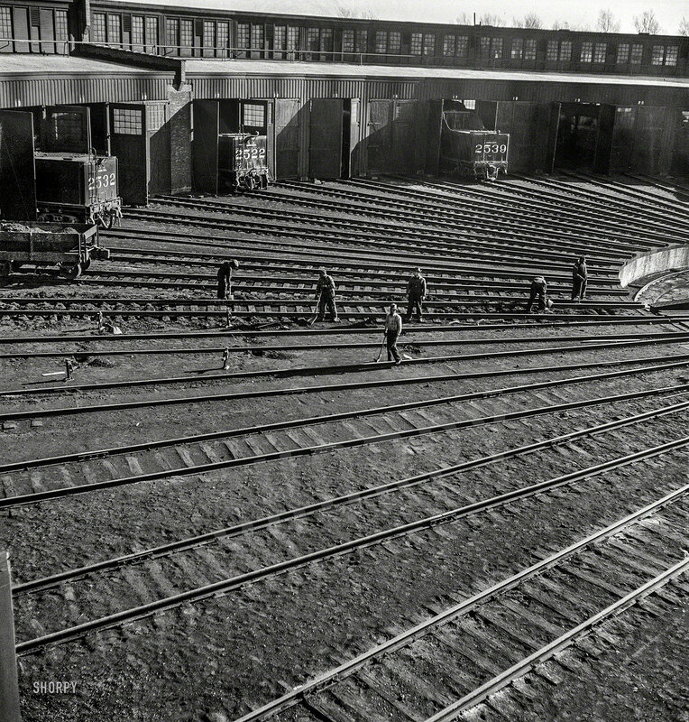November 1942. Track crews repairing tracks in the roundhouse at the Illinois Central rail yard, Chicago