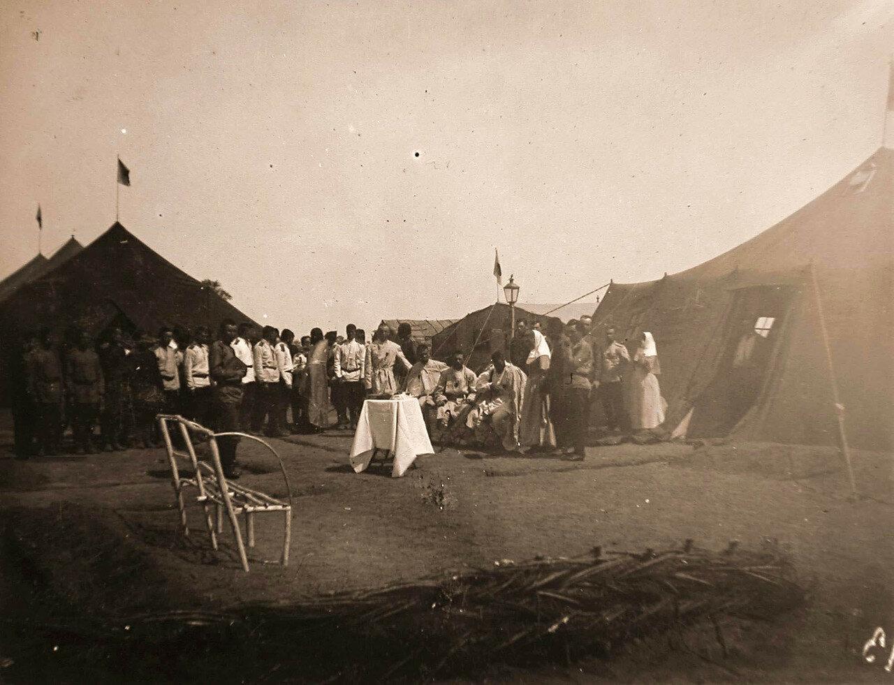 28. Раненые и медицинский персонал у палаток полевого лазарета во время молебна