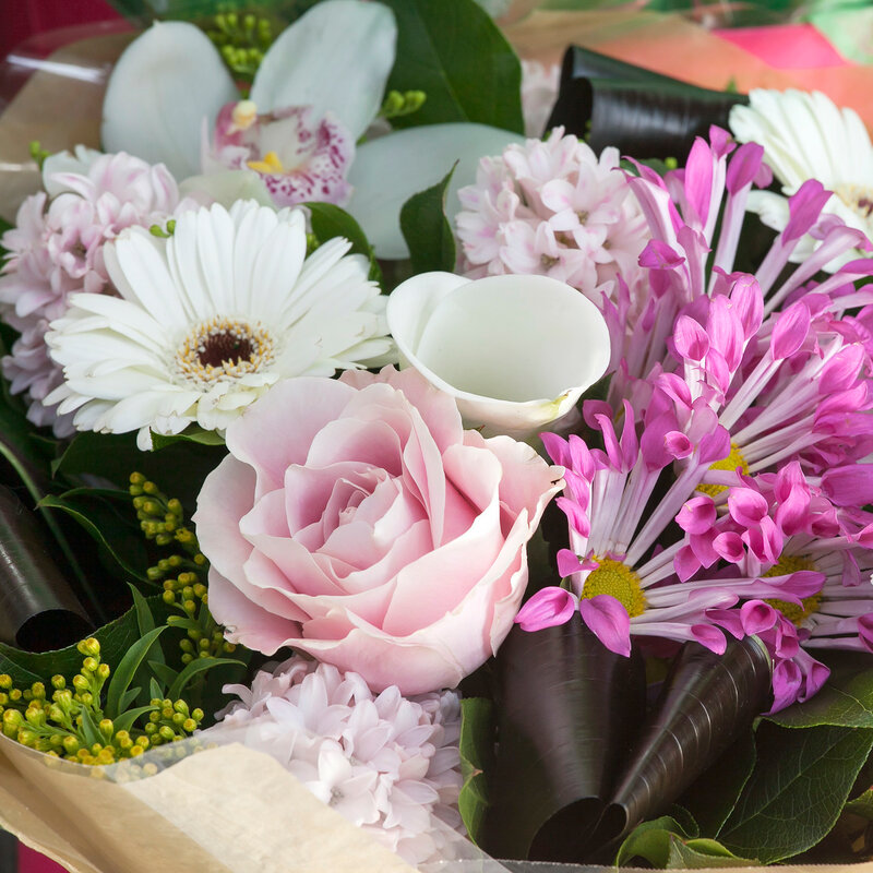 Pink-white bouquet of rose, calla, hyacinth, gerbera in kraft paper