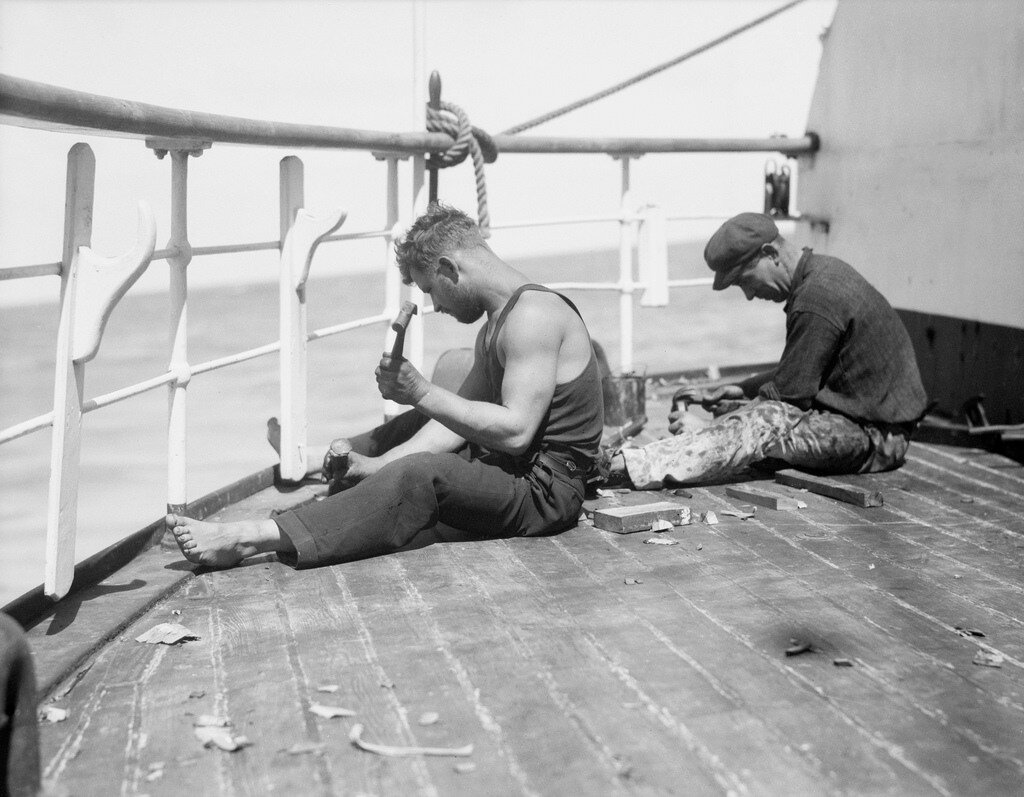 1933 Two of the crew sitting right aft on the starboardside of the poop, renewing the caulking or a smallarea of decking.