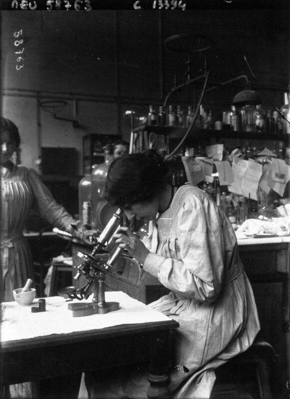 Woman looking through a microscope at the municipal laboratory Paris France