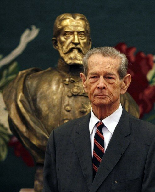 Romania's former King Michael poses next  to newly unveiled bronze sculpture of King Carol I, the founder of Romania's royal dynasty, after addressing address parliament in Bucharest