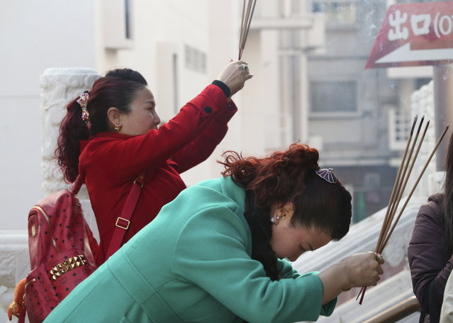 Visitors hold joss sticks as they offer prayer at a temple in China Town in Yokohama, near Tokyo, Mo