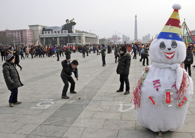 North Korean boys spin a top as they gather at Kim Il Sung Square for Lunar New Year in Pyongyang, N