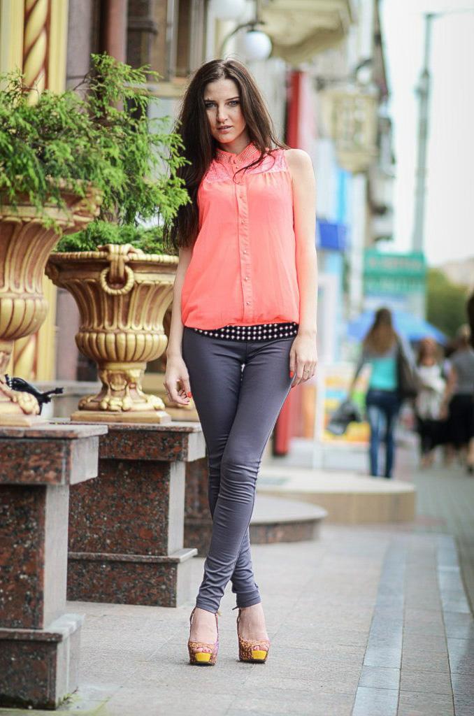 Длинноволосая девушка в узких джинсах на каблуках