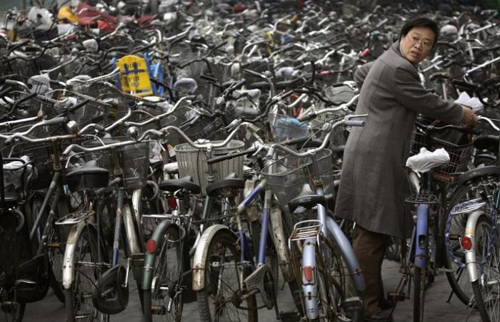 Женщина забирает свой велосипед на стоянке за станцией метро в Пекине. 7. В метро