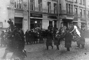 Группа демонстрантов с венками проходит по 7-й Рождественской улице.