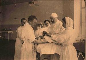 Профессор И.Х.Дзирне(справа),доктор Туревич(слева) и сёстры милосердия во время проведения операции раненому в голову.