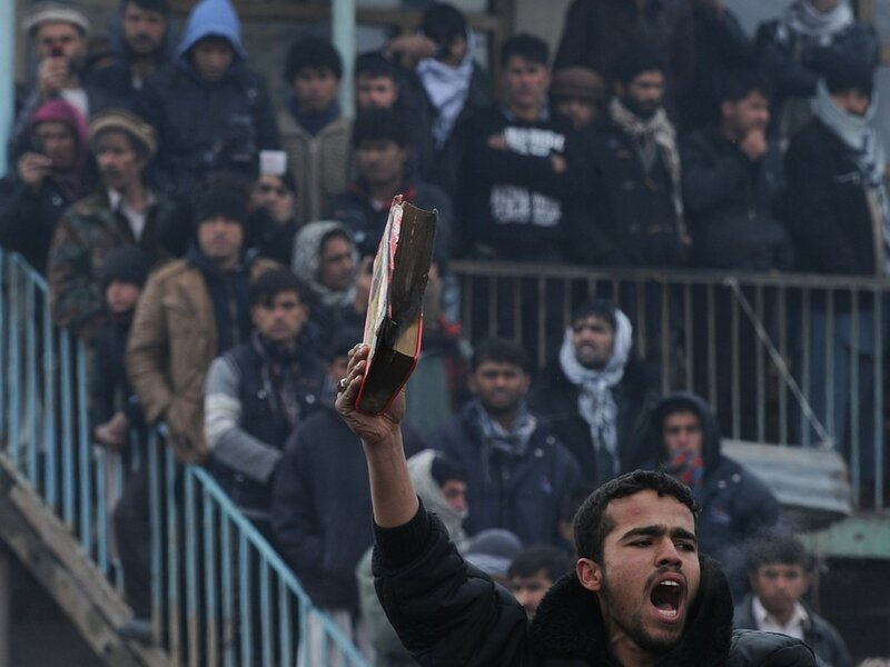An Afghan demonstrator holds a copy of a