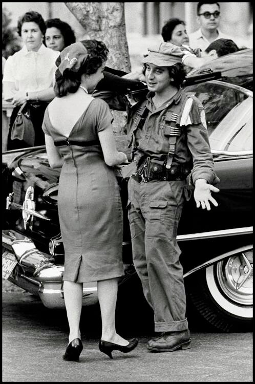 Havana, Cuba, 1959. A young soldier speaking to a woman during the revolution.