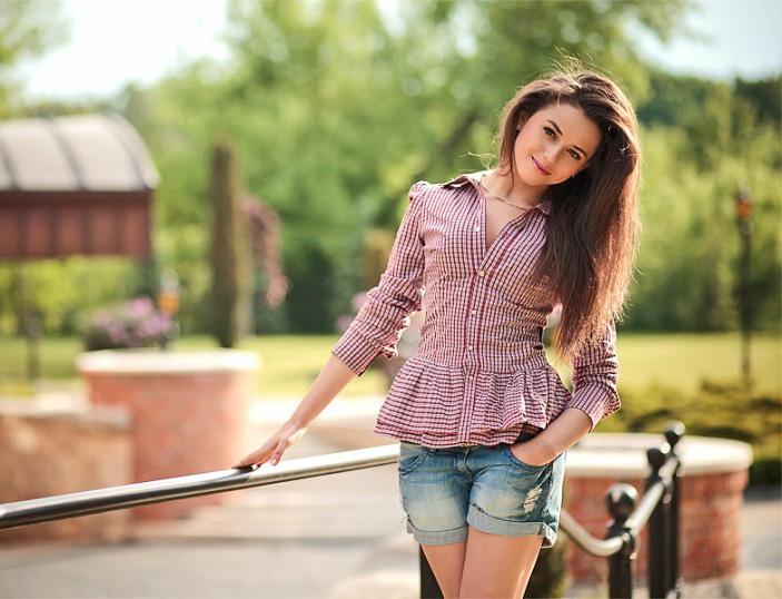 Пышноволосая девушка в мини-шортах на скамейке