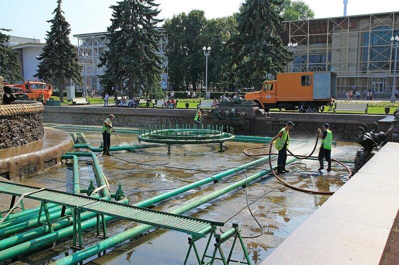 Рабочие чистят бассейн фонтана Каменный цветок на ВДНХ при помощи воды под большим давлением
