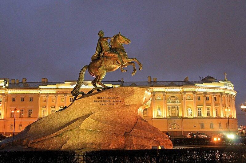 Медный всадник — памятник Петру I на Сенатской площади в Санкт-Петербурге. Вечерний вид, подсветка фонарями, на фоне здания Конституционного суда РФ.