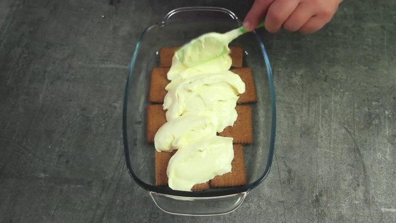 4. Выкладывайте печенье и крем слоями. По желанию можно положить между слоями фрукты, к примеру