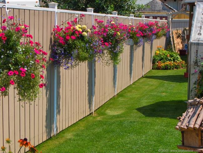 Забор вовсе недолжен быть однообразным. Например, его можно украсить кашпо с цветами .