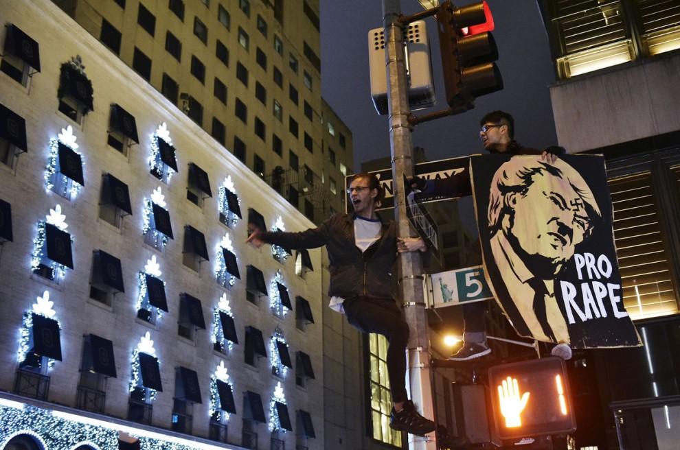 Демонстранты на 5-й авеню возле небоскрёба Трамп-тауэр в Нью-Йорке, 9 ноября 2016 года. Надпись на т