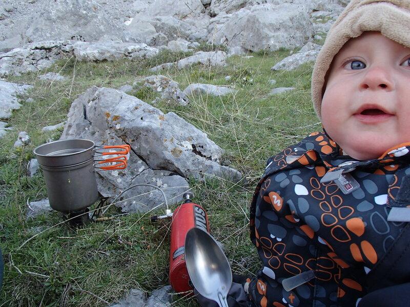 ребенок с ложкой ждет ужина у бензиновой горелки