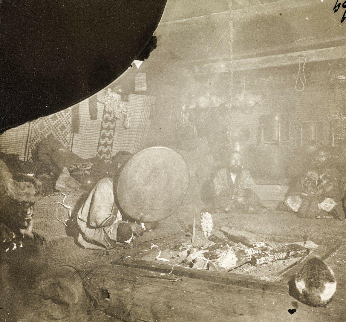 Шаман и айны, сидящие вокруг костра