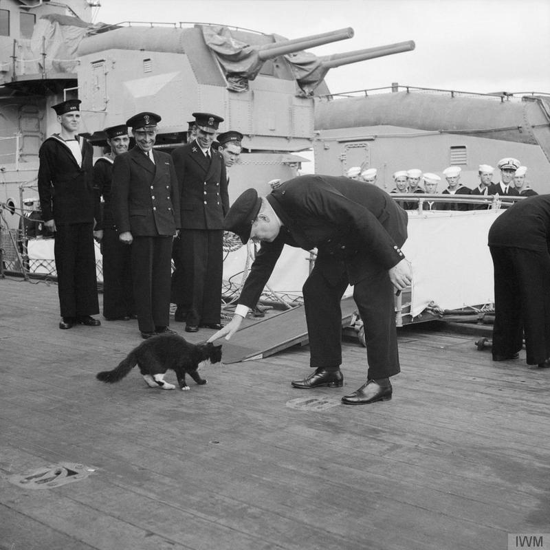 Churchill restrains Blackie the cat, the mascot of HMS PRINCE OF WALES, from joining an American destroyer, while the ship&'s company stand to attention during the playing of the National Anthem. August 1941.