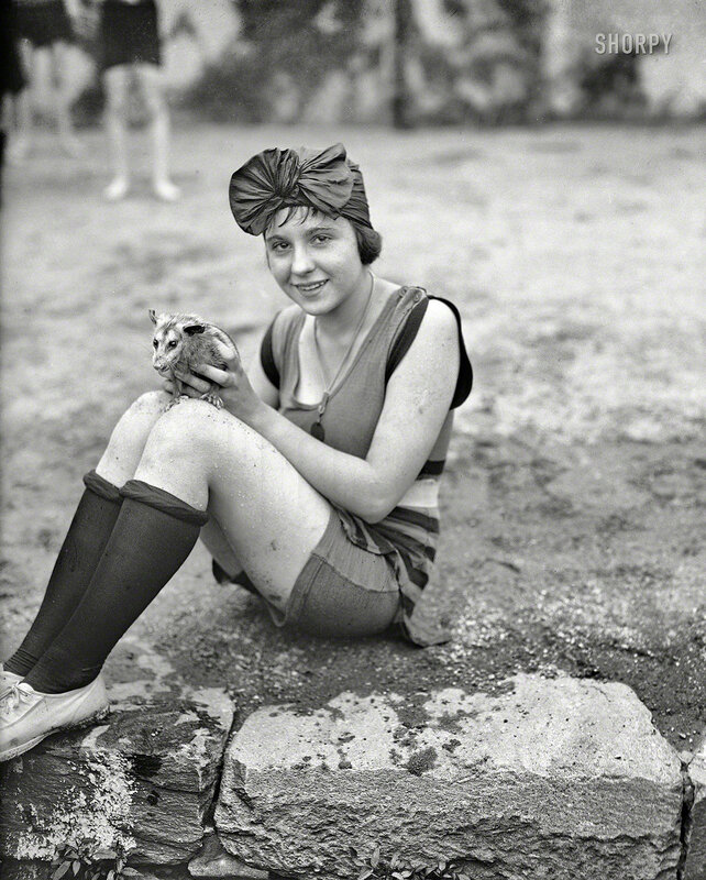 July 1922. Washington, D.C. Snapped at the Tidal Basin. Mildred Kapleck with her pet opossum, the latest novelty introduced at the bathing beach.