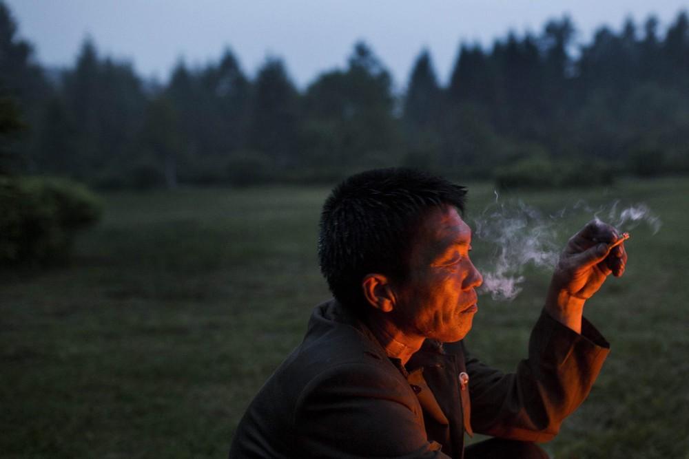 9. Кореец жарит картофель и курицу на костре в провинции Янгандо. (Photo by David Guttenfelder / AP