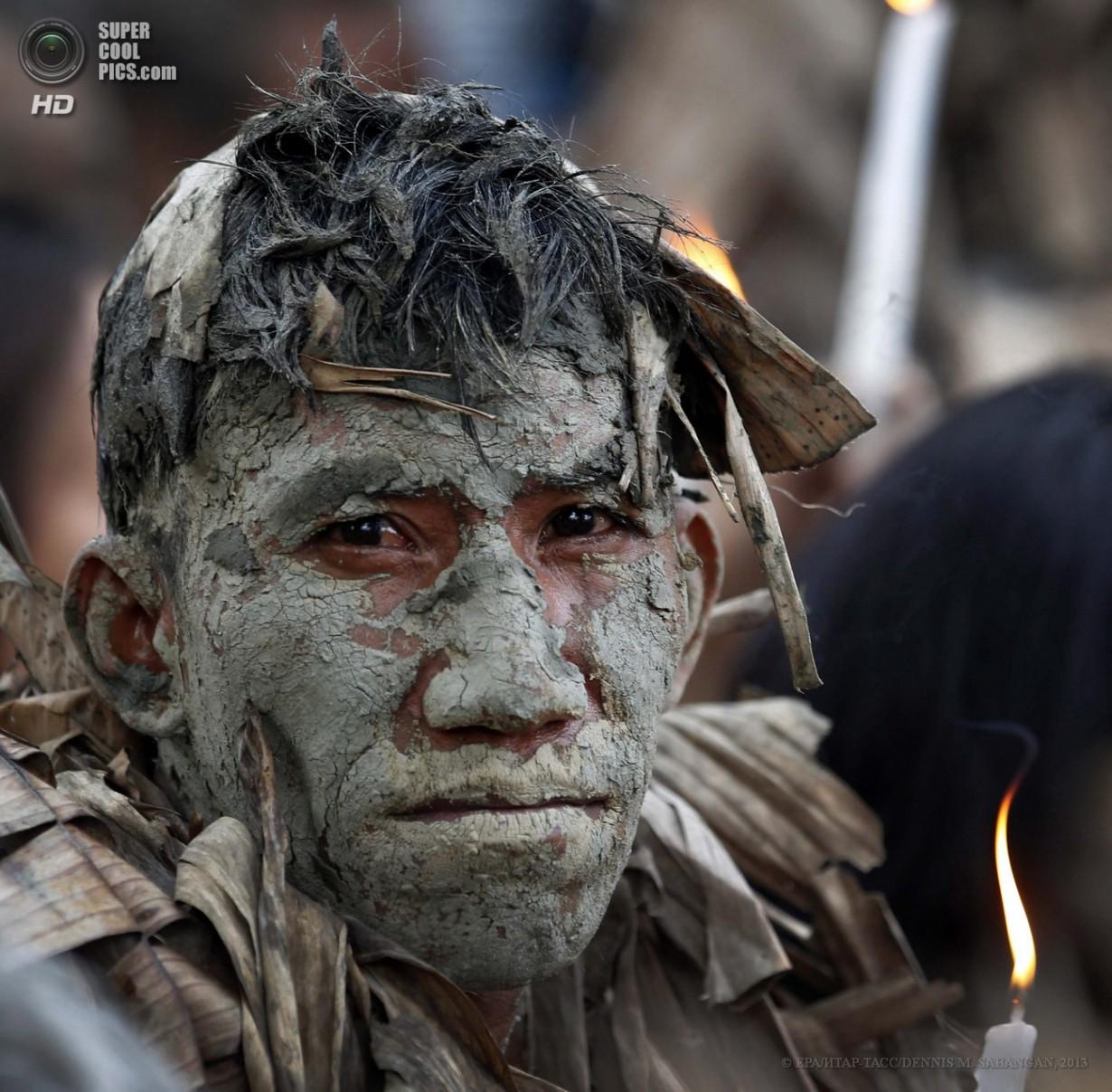 Филиппины. Алиага, Нуэва-Эсиха. 24 июня. Филиппинский католик, покрытый грязью и одетый в сухие
