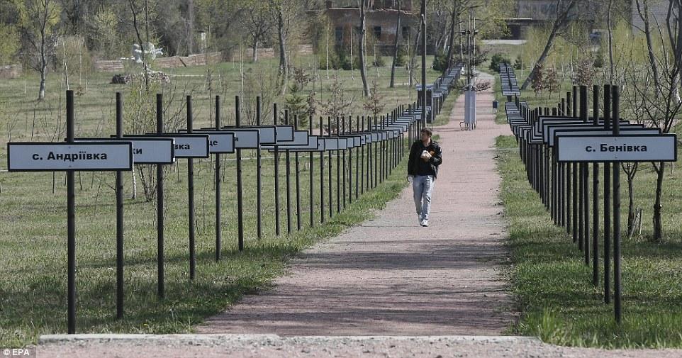 Мужчина прогуливается мимо дощечек с названиями заброшенных деревень.