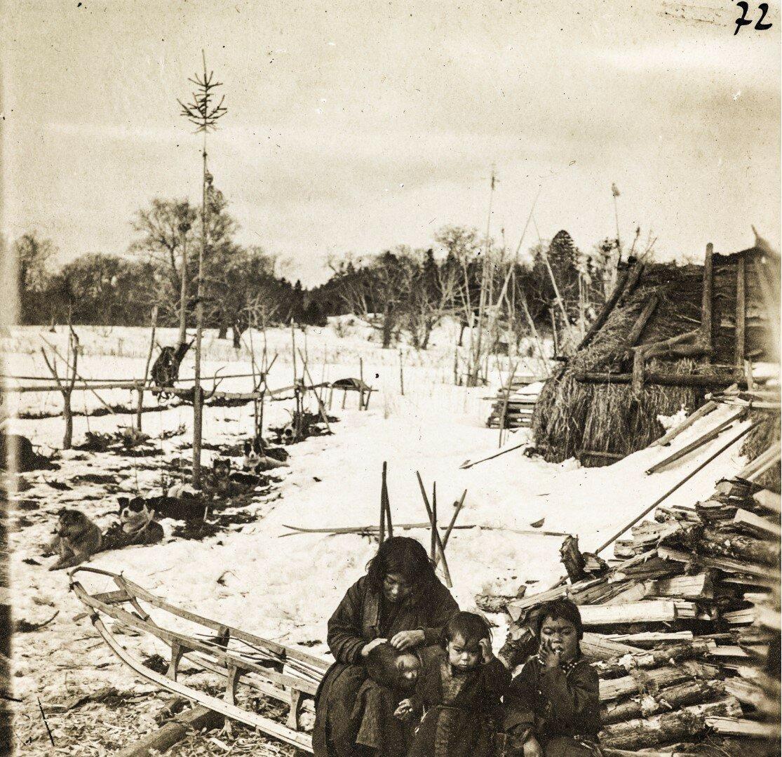 Женщина и дети айнов возле хижины зимой