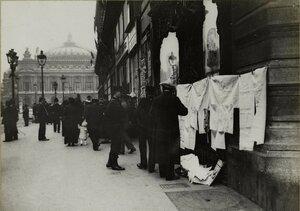 1914. Напротив Оперы возле большого дома лоточник продает ткань. 03.10
