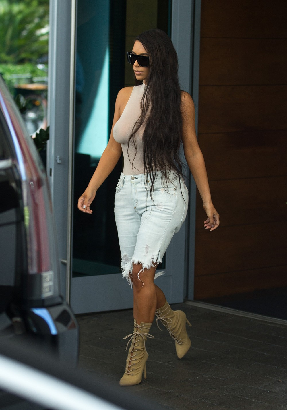 Kim Kardashian heads out in Miami wearing a see-through nude color top.