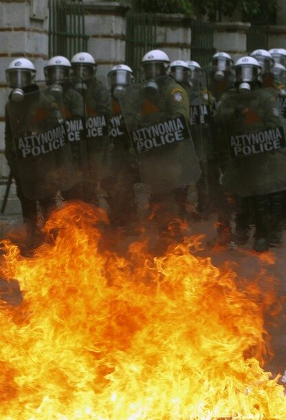A group of riot policeman is stopped by flames caused by a petrol bomb thrown by protesters during clashes in central Athens