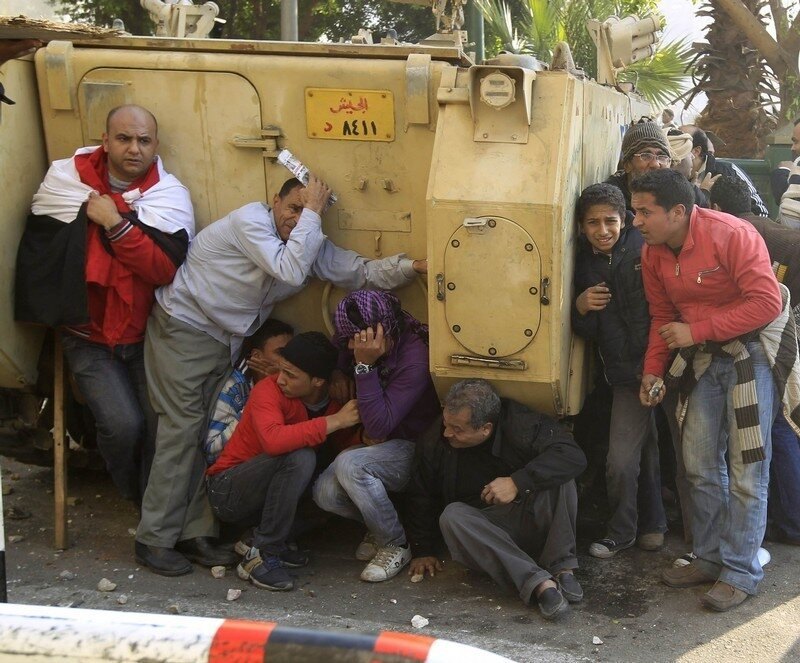 Demonstrators take cover during rioting between pro and anti Mubarak supporters in Tahrir Square in Cairo