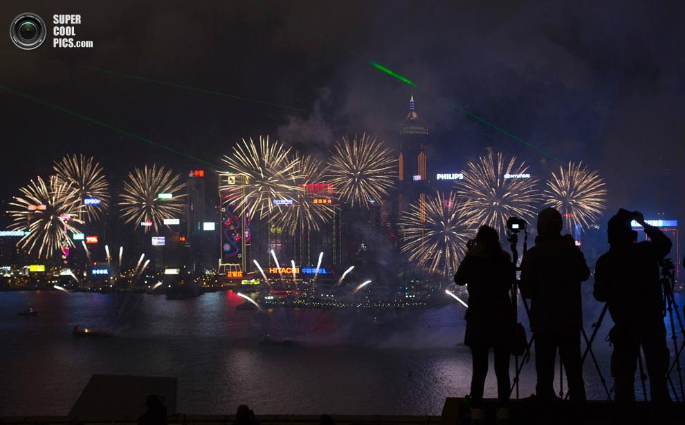 Фотографы снимают праздничный фейерверк надзаливом Виктория,Гонконг. (REUTERS/Tyrone Siu)