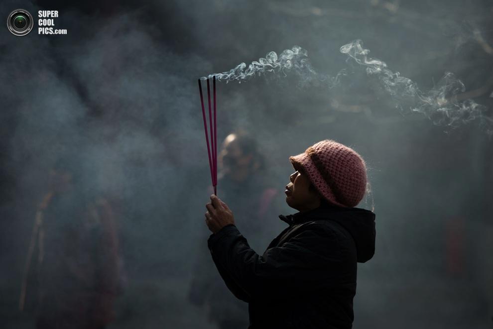 Женщина во время молитвы в храме Юнхэгун.(ED JONES/AFP/Getty Images)