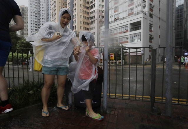 People brave the wind on the waterfront as Typhoon Haima approaches in Hong Kong, Friday, October 21