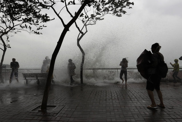 People play with overflown water caused by Typhoon Haima in Hong Kong, Friday, October 21, 2016. (Ph