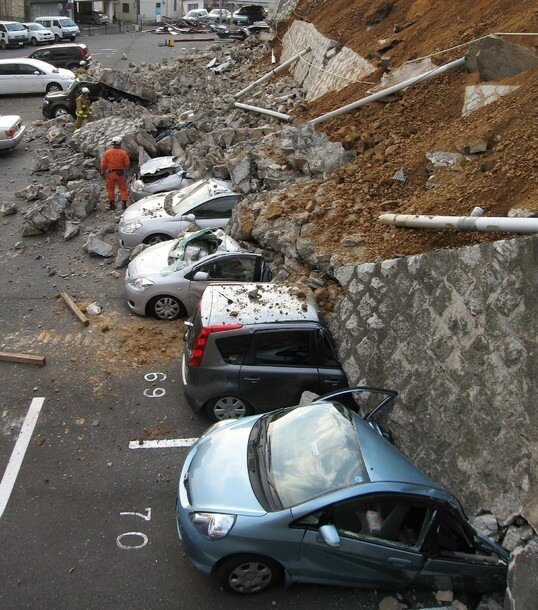 Vehicles are crushed by a collapsed wall